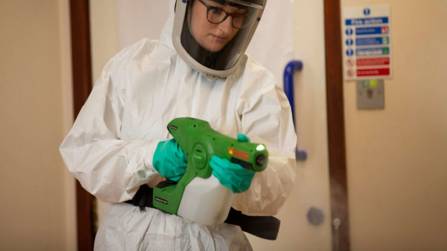 SafeGroup operative spraying disinfectant in office